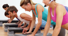 Aerobics class doing press ups together led by instructor - stock footage