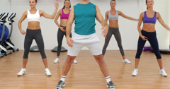 Aerobics class stretching together led by instructor Stock Footage