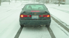 Car going down icey road Stock Footage