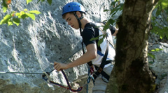 Guy in alpinist gear moves the clip on the steel safety wire Stock Footage