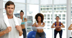 Fitness class squatting on bosu balls while instructor smiles at camera Stock Footage