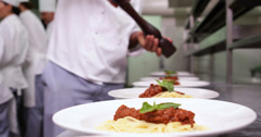 Chef seasoning spaghetti dinners with black pepper Stock Footage