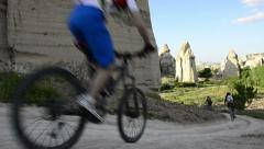 Outdoor bikers ride bicycle on hoodoo land in Cappadocia Stock Footage