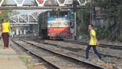 TRAIN LOCOMOTIVE: Red and blue train approaches among pedestrians - stock footage