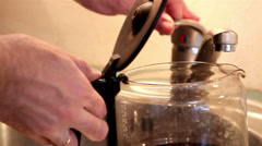 turning on the faucet and putting water on the coffeemaker - stock footage