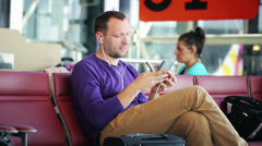 Happy man with cellphone listening music on the airport - stock footage