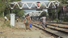 TRAIN - LOCOMOTIVE: Women walk train track with distant train approaching Stock Footage