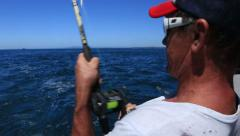 Man Game fishing off back of boat Stock Footage