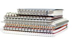 multi colored spiral notepads on white background background - stock photo