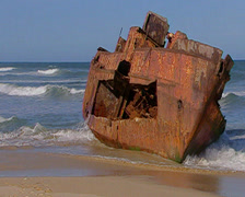 A shipwreck on Port Alfred beach as waves lap at it Stock Footage