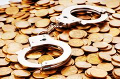 Hand cuffs and coins as security concept Stock Photos