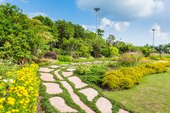 colourful flowerbeds and winding grass pathway in an attractive - stock photo