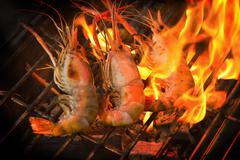 Grilled prawns on flaming in seafood restaurant Stock Photos