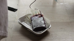 Donor giving blood,plastic bag with blood tilt up to arm,close up Stock Footage