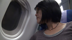 Chinese woman looking through plane window Stock Footage