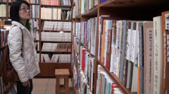 Asiatic woman searching in a bookshop - stock footage