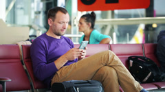 Happy man with cellphone sitting on the airport Stock Footage