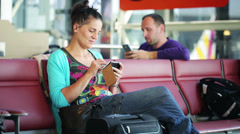 Woman with cellphone waiting on the airport - stock footage