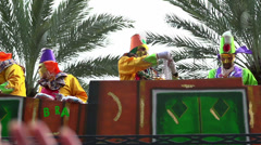 Krewe on float throwing beads in slow motion Stock Footage