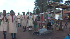Kenya scouts walking down a dirt road next to a wood building Stock Footage