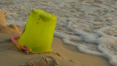 Children's Yellow Sand Pail on Beach With Tide Coming In Stock Footage