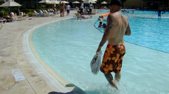 Man with tattoos walks around the edge of pool at resort Stock Footage