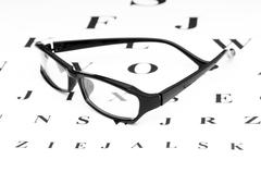 Optical reading glasses on the eyesight table - stock photo