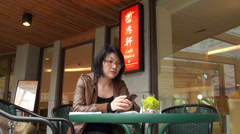 Asiatic woman in a coffee shop Stock Footage