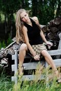 the resting young girl in the woods. long hair dispelled by wind - stock photo