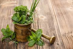 herbs with antique mortar - stock photo