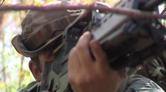 Soldier with gun hiding in bushes Stock Footage
