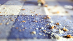 Close up of crumbs falling down on blue checked tablecloth. Stock Footage