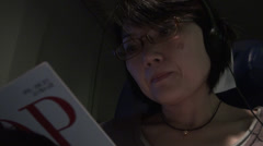 Chinese woman reading a book during a fly Stock Footage