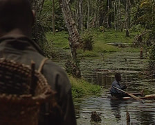 Pygmy male on hand made canoe whilst his freind watches - stock footage