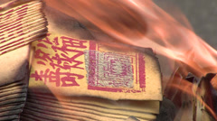 Asian people burning money in a religious celebration Stock Footage