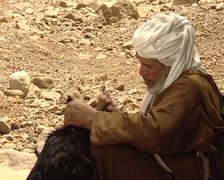Berbers man taking water from a well in sahara desert Stock Footage