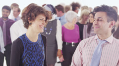 Cheerful businessman & woman standing in front of large diverse group of people - stock footage