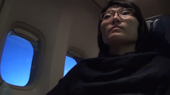 Chinese woman listen to music during a fly Stock Footage