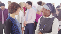 2 cheerful businesswomen standing in front of large diverse group of people - stock footage