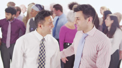 2 cheerful businessmen standing in front of large diverse group of people - stock footage