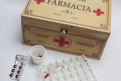 pills with pill organizer next to old wood kit - stock photo