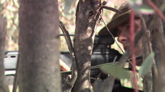 Soldier holding a gun order hiding behind tree Stock Footage