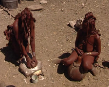 Himba grinding wheat Stock Footage