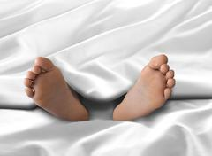 Feet under white blanket and bed sheet Stock Photos