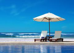 Two chairs with white umbrella near the beach Stock Photos