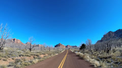 POV Time lapse vehicle road trip extreme terrain winter snow blue sky Zion Utah - stock footage
