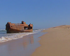 Rusty shipwreck on Port Alfred beach as waves lap at the ship, Port Alfred Stock Footage