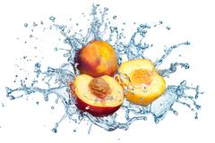 peach in spray of water. - stock photo