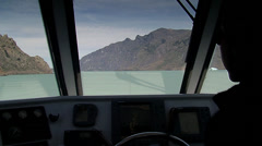 Inside of a boat's cabin, captain driving and Calafate lake at the background Stock Footage