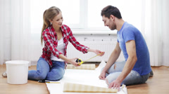 Smiling couple measuring wallpaper Stock Footage